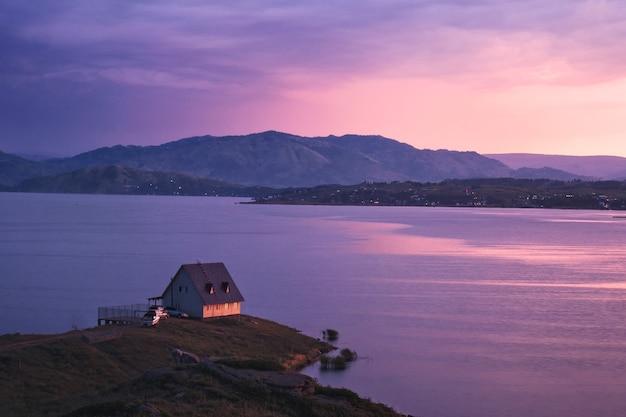 日没時の湖のほとりにある家、カザフスタン東部、ブクターマ貯水池