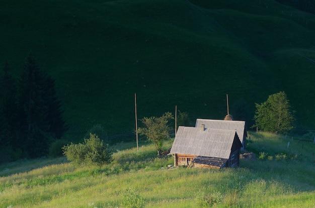 山の村の日当たりの良い牧草地の家