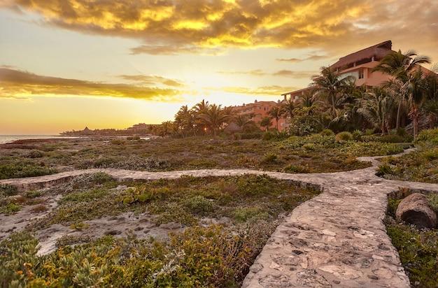 オレンジ色の時代にメキシコのプエルトアベンチュラスの海と岩の多い海岸を見下ろす家:息をのむようなカリブ海の風景の上の燃えるような空。