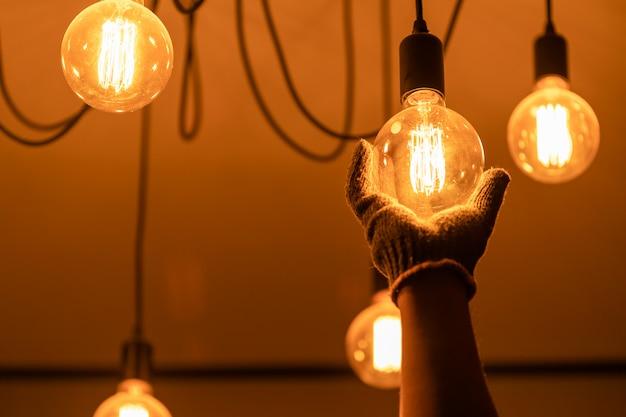 Владелец дома меняет винтажную лампочку