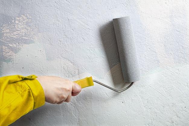 노란색 정장을 입은 집 화가는 페인트 롤러를 사용하여 회색으로 벽을 그립니다.