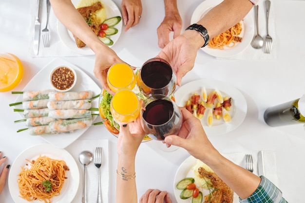 House party guests toasting with glasses or orange juice and red wine at party, top view