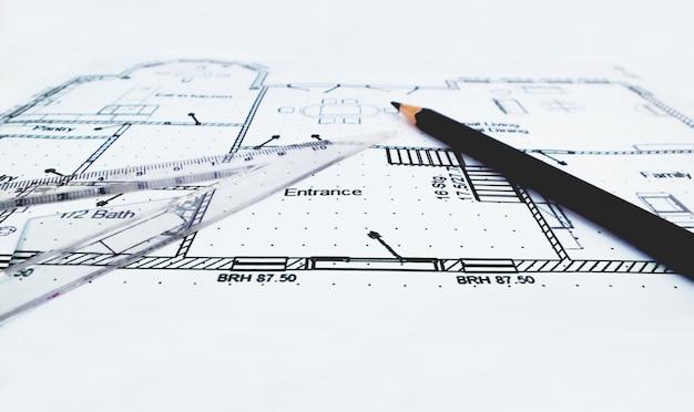 План дома и инструменты для рисования с установленной квадратной линейкой и карандашом
