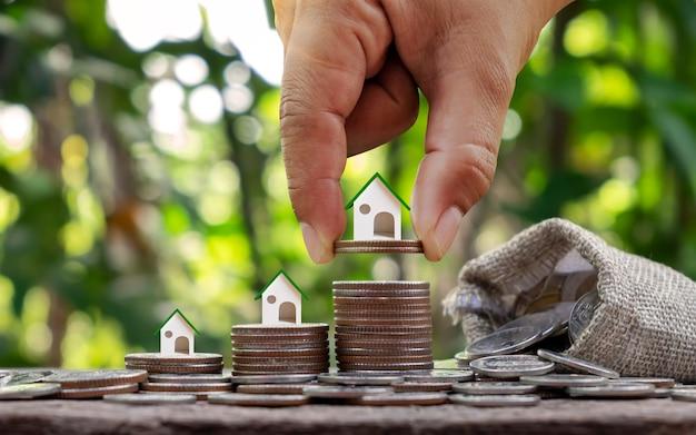 コインの山と金融コンセプトのコインハンドの家の計画。高成長投資と不動産投資