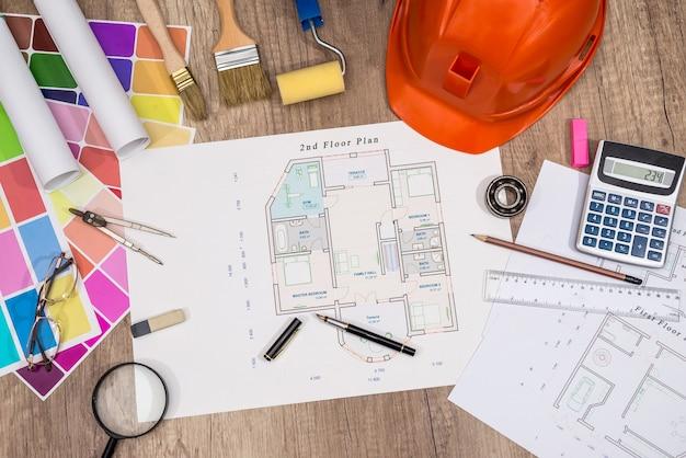 Проект дома со строительным шлемом, цветовой палитрой и инструментами для рисования