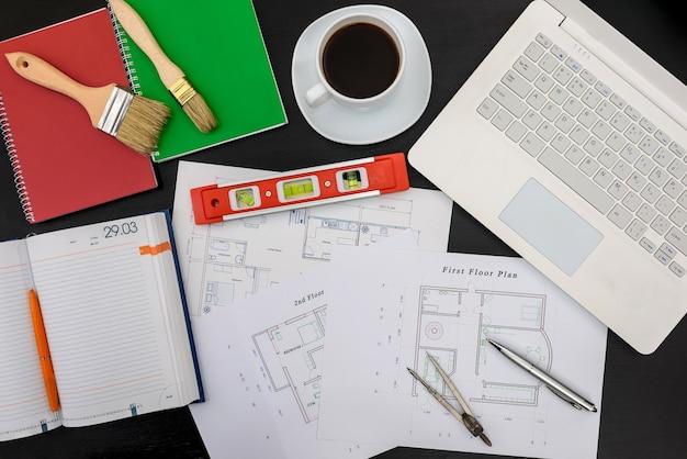 Проект дома с инструментами, ноутбуком и блокнотом