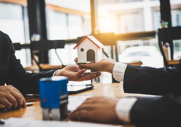 주택 부동산 판매 에이전트는 주택 구매자 대출에 대해 승인 된 문서를 검토합니다.