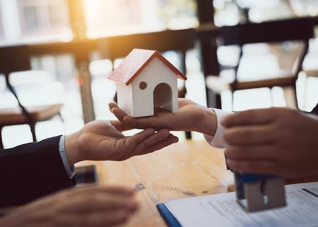 주택 부동산 판매 에이전트는 주택 구매자 대출에 대해 승인 된 문서를 검토합니다. 프리미엄 사진