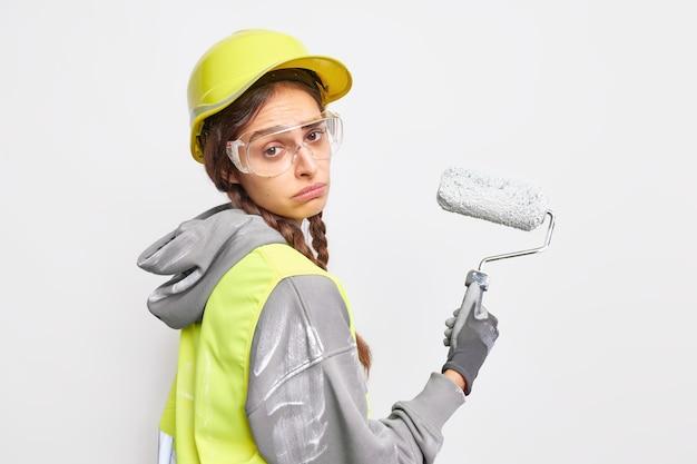 집 리모델링 및 재장식 개념입니다. 슬픈 피곤한 여성 건축업자는 페인트 롤러를 들고 벽을 칠하기 위해 건설 도구를 사용합니다