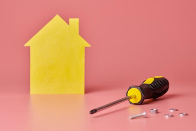 Концепция ремонта дома. ремонт дома и косметический ремонт. винты и желтый дом в форме фигуры на розовом фоне.