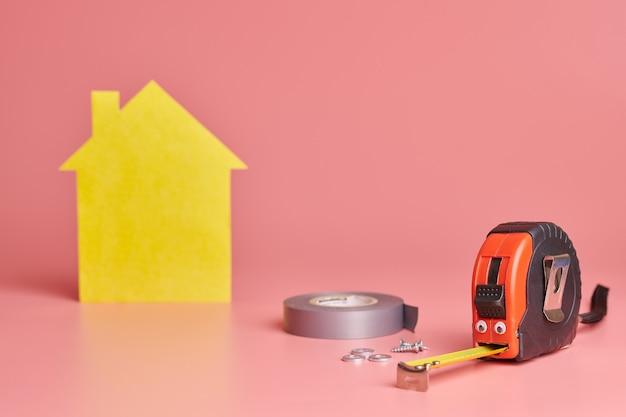 Забавная концепция ремонта дома. металлическая рулетка и другие предметы ремонта. ремонт дома и косметический ремонт.