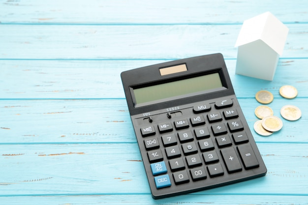 House resting on calculator concept for mortgage calculator, home finances or saving for a house.