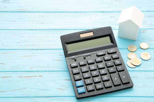 住宅ローン電卓、家計簿または家のための節約のための電卓のコンセプトで休む家。