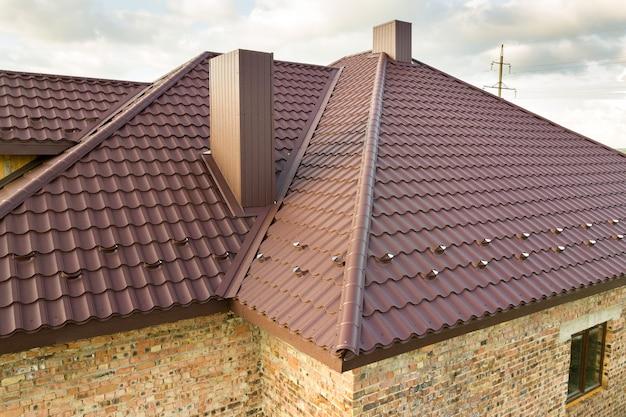 Конструкция крыши дома покрыта листами металлочерепицы коричневого цвета