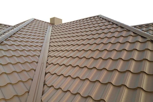 Поверхность крыши дома покрыта металлической черепицей коричневого цвета.