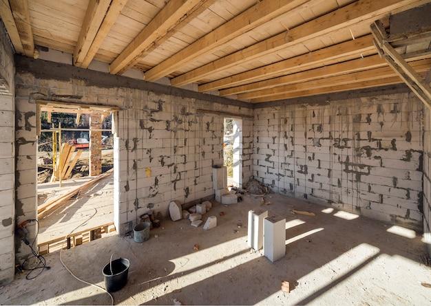 주택 건설 및 공사중 인테리어. 중공 폼 단열재 블록, 목재 천장 보 및 지붕 프레임의 에너지 절약 벽.