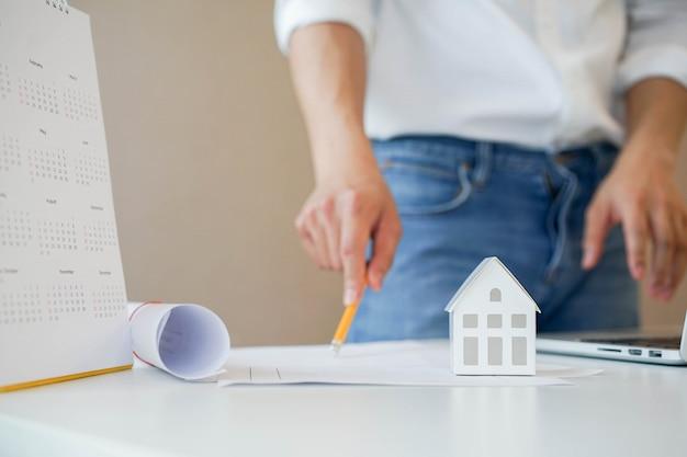 プロの建築家がオフィスのテーブルに家のモデルは、プロジェクトを計画するための青写真に取り組みます