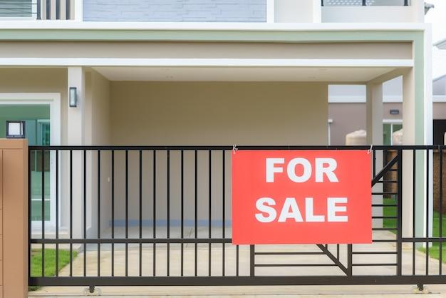 Знак продажи дома висит на заборе двери дома, чтобы сообщить заинтересованным сторонам для контакта.