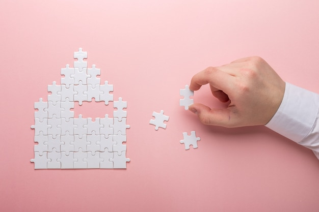 House shape puzzle the concept of rent, mortgage hand holding piece of white puzzle