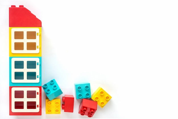 House of small and big plastic constructor bricks on white background. popular toys.