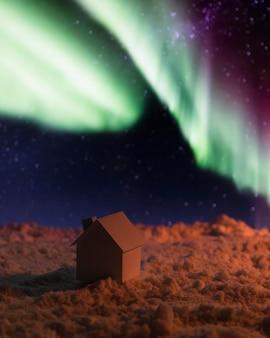 Casa sulla neve con aurora boreale