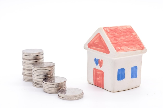 House and stack coins on white background