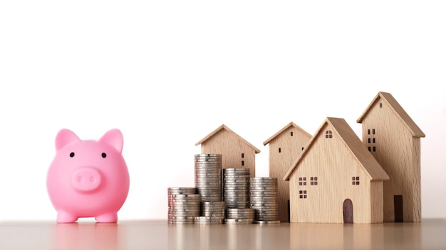 House and stacking coins saving growth with piggy bank isolated and white background