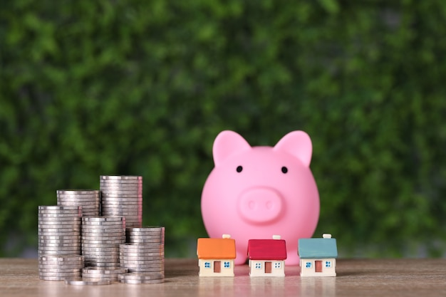 House and stacking coins saving growth with piggy bank on wooden desk and green.