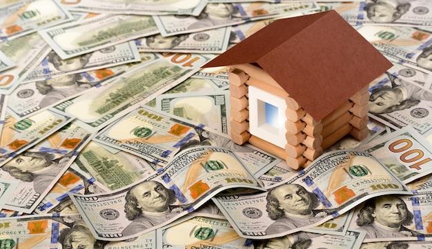 ドル札の山の上に立っている家。投資、不動産、不動産のコンセプト