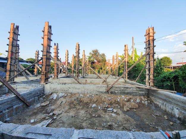 집 구조 건설 시멘트 바닥을 붓고 시멘트 기둥을 이미 붓습니다. 하늘을 배경으로 합니다.