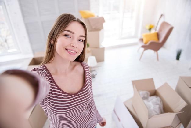 新築祝いの自撮り。新しいアパートに引っ越して自分撮りをして友達と共有したい美しい若い女性