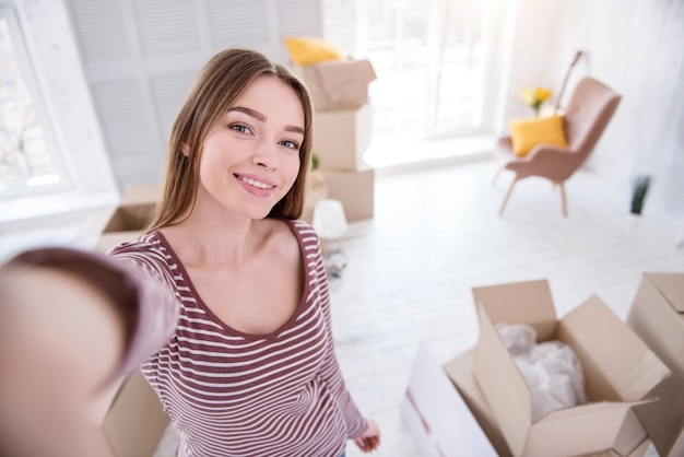 House-warming selfie. beautiful young woman taking a selfie having moved in to a new flat and wanting to share it with her friends