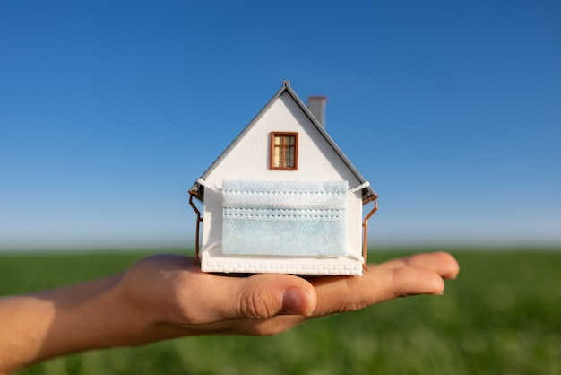 House wearing protective mask in hand against spring green field and blue sky surface