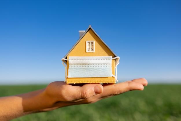 Дом в защитной маске в руке против весеннего зеленого поля и поверхности голубого неба
