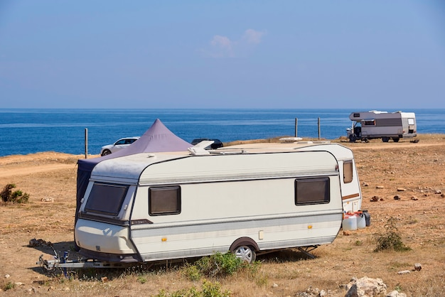 The house on wheels is parked on the beach in front of the blue sea.