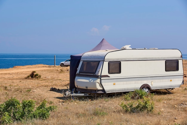 The house on wheels is parked on the wild beach.