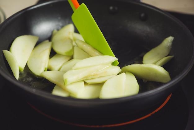 앞치마를 입은 주부 만들기. 사과 케이크 요리를 만드는 단계. 녹색 사과 절단.