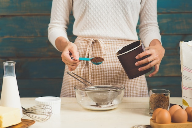 エプロン作りをしている主婦。料理のチョコレートケーキを作る手順。
