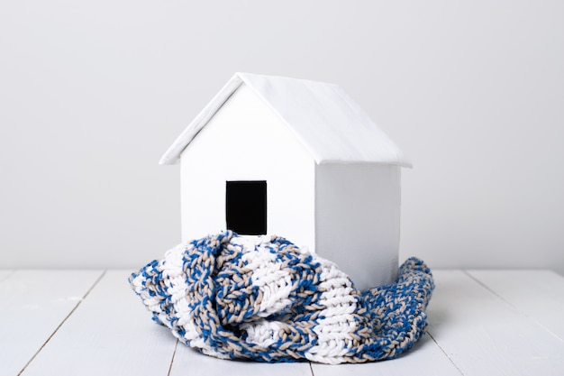 House in winter - model of a house wearing a knitted scarf