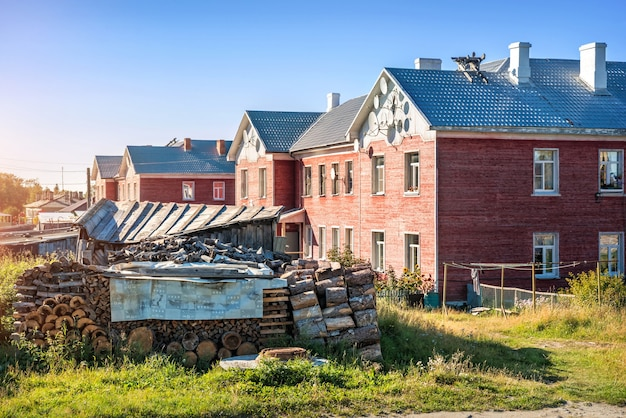 House with antennas on the facade on the solovetsky islands and a large firebox with logs in the yard