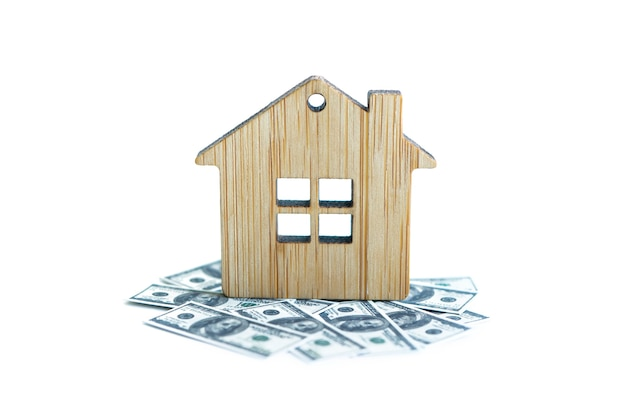 House with a foundation on a hundred dollar bill. a toy house with a roof costs money. concept: mortgage, purchase, sale of real estate, rental housing
