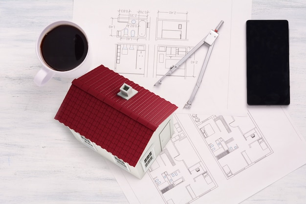 House with house plan, coffee and smartphone.