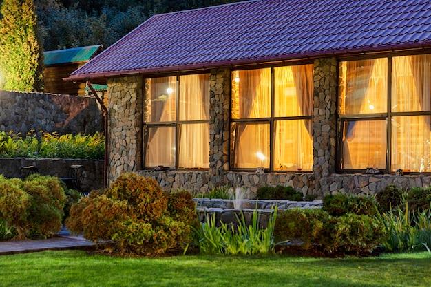 自然の夜に明るい窓のある家。心地よさと快適さ。