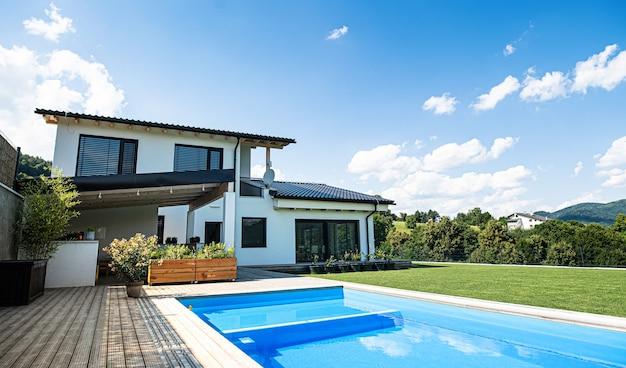 Дом с бассейном на открытом воздухе в саду на заднем дворе в сельской местности.