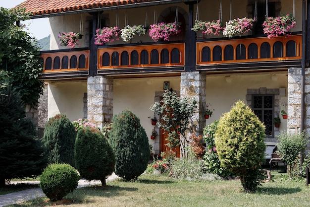 夏の開花庭園にある瓦屋根の家