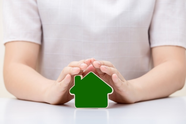 House under woman's hands. insurance and house protection concept.