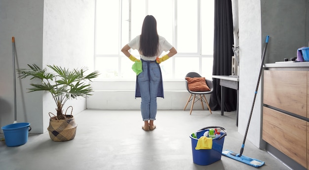 Вид сзади работы по дому молодой женщины в желтых резиновых перчатках, держащей тряпку и