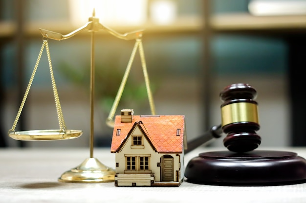 不動産法の概念。テーブルの上の裁判官小houseと家モデル