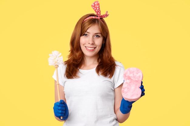 ハウスクリーニングのコンセプトです。陽気な肯定的な若い女性は家で春の大掃除を行い、ブラシとスポンジを保持し、カジュアルな服装と保護手袋を着用し、職務が好きで、黄色の壁の上に立っています。