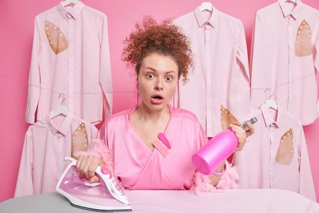 家庭とアイロンのコンセプト。驚いた唖然とした巻き毛の主婦は洗剤スプレーアイロンを持っています家族の服は口を開いたままピンクのガウンに身を包んだ毎日の家庭のルーチンをしています
